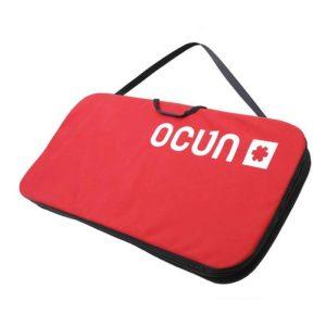 Das Bild zeigt die Ocun Sitcase Bouldermatte. Das kleine rote Crashpad liegt schräg im Bild, man erkennt den Schulterriemen und das Logo am Pad.