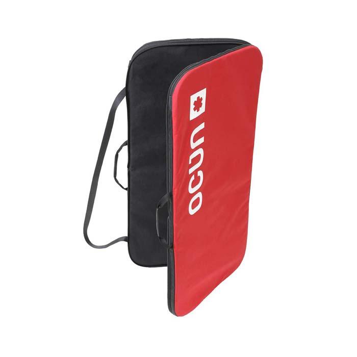 Das Bild zeigt die Ocun Sitcase Bouldermatte. Das Crashpad steht leicht aufgeklappt in Bildmitte. Man erkennt die schwrze Innenseite, die zwei Trageriemen, den Schulterriemen und die rote Außenseite mit dem Logo.