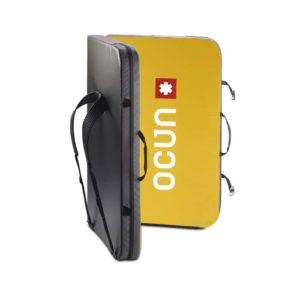 Das Bild zeigt die Ocun Sundance Bouldermatte. Das Pad steht leicht aufgeklappt in Bildmitte. Man erkennt die gelbe Innenseite, die zwei Trageriemen, den Schulterriemen und die schwarze Außenseite mit dem Logo.