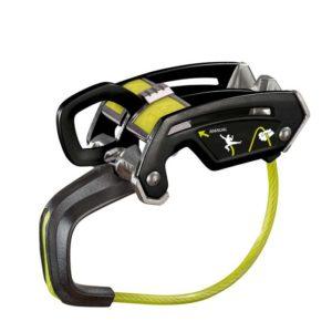 Das Bild zeigt das Edelrid Giga Jul Sicherungsgerät. Es liegt in Bildmitte, man blickt von leicht links oberhalb darauf. Man erkennt das Gerät mit dem gelbem Drahtbügel an der Unterseite, dem schwarzen Körper, die beiden Seilschlitze sowie den gelben Schieber für die beiden Sicherungsmodi.