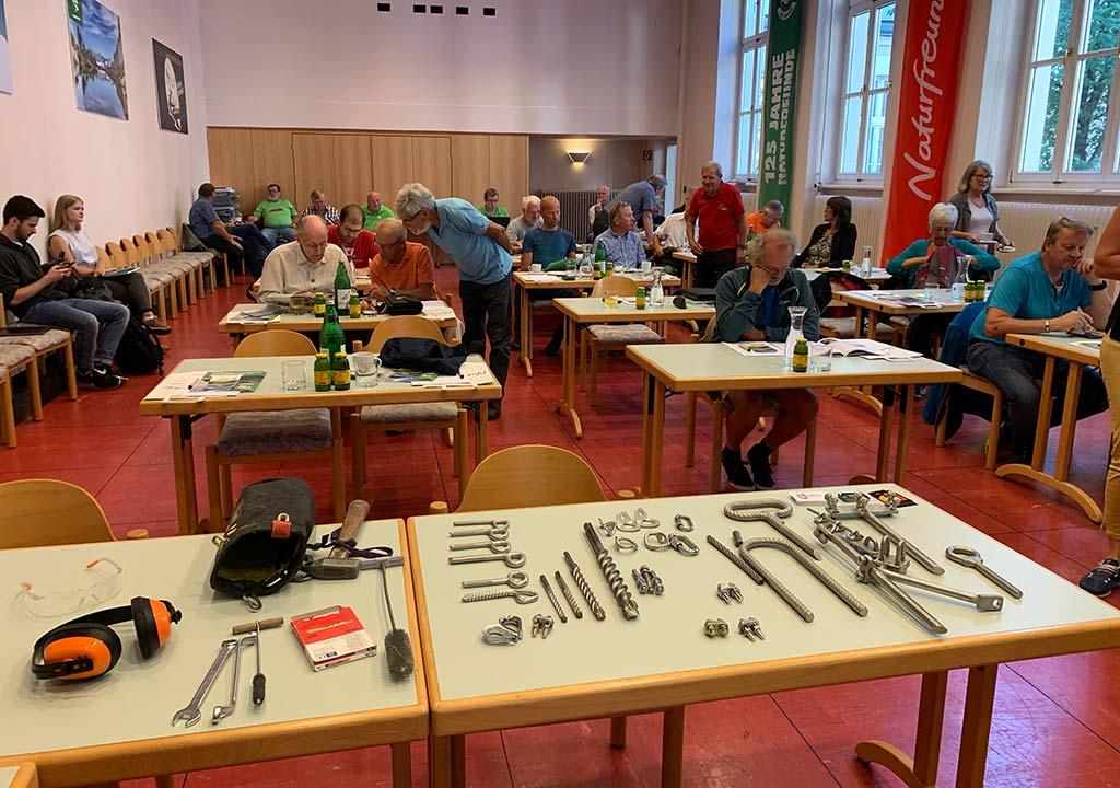Das Bild zeigt eine Szene eines Einbohr Workshop von bolting.eu. Auf einem Tisch liegen vielerlei Einbohr Hardware, im Hintergrund dahinter viele Tische mit Workshop Teilnehmern.