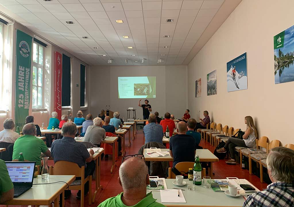Das Bild zeigt einen Einbohr Workshop von bolting.eu. Im Vordergrund sind Teilnehmer an Schreibtischen sitzend zu sehen, im Hintergrund trägt Gerhard Schaar vor einer Leinwand vor.