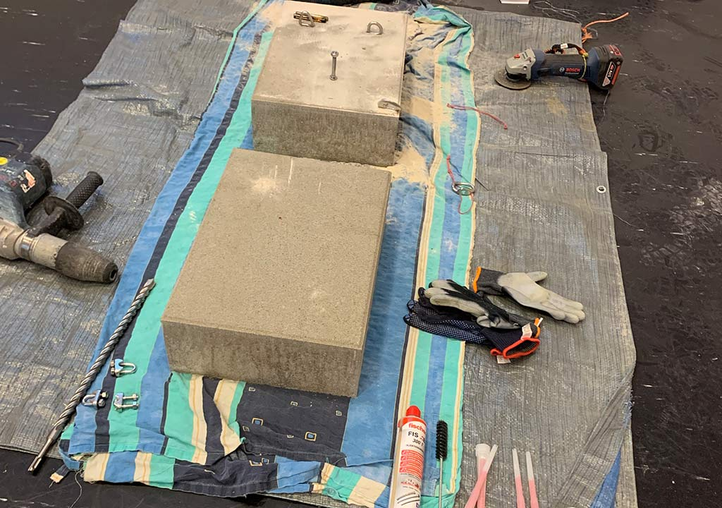 Das Bild zeigt zwei Betonblöcke am Boden auf einer Plane bei einem Einbohr Workshop von bolting.eu.