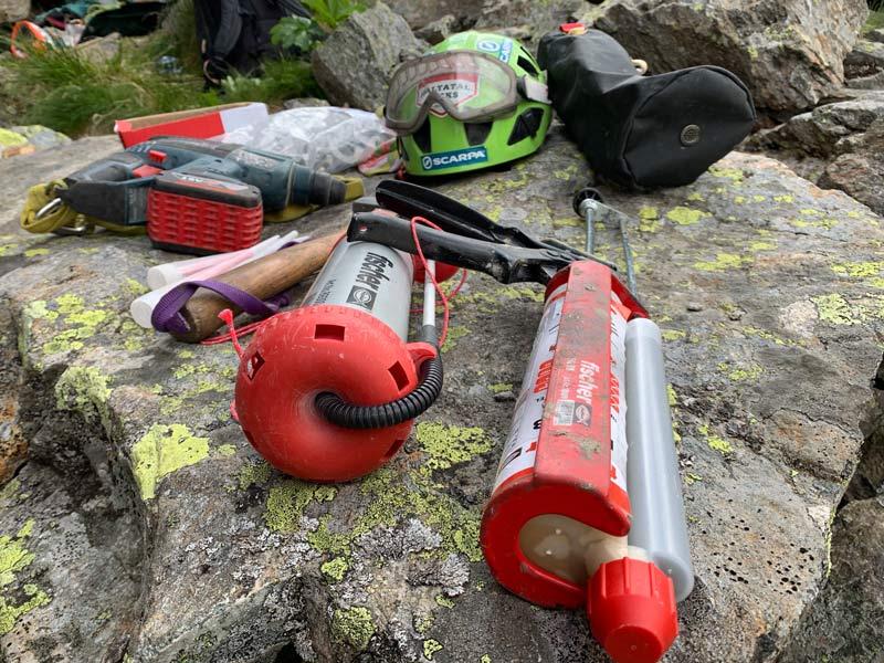 Das Bild zeigt eine Injektionsmörtel Kartusche in einer Auspresspistole zum Klebehaken setzen. Im Hintergrund ein Ausbläser, Hammer und Kletterhelm mit Schutzbrille.