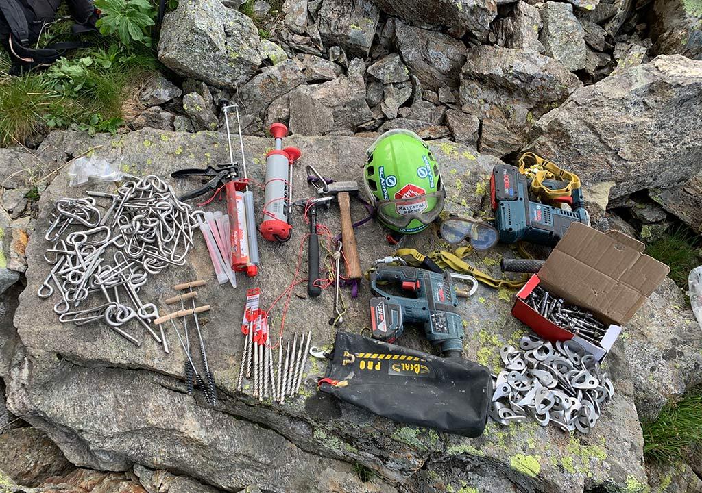 Das Bild zeigt eine Ansammlung an Einbohr Materialien bei der Klettergarten Sanierung. Zu sehen sind auf einem großem Stein Bohrhaken, Klebehaken, Inhejktionsmörtel, Helm, Materialtaschen, SDS Bohrer usw.