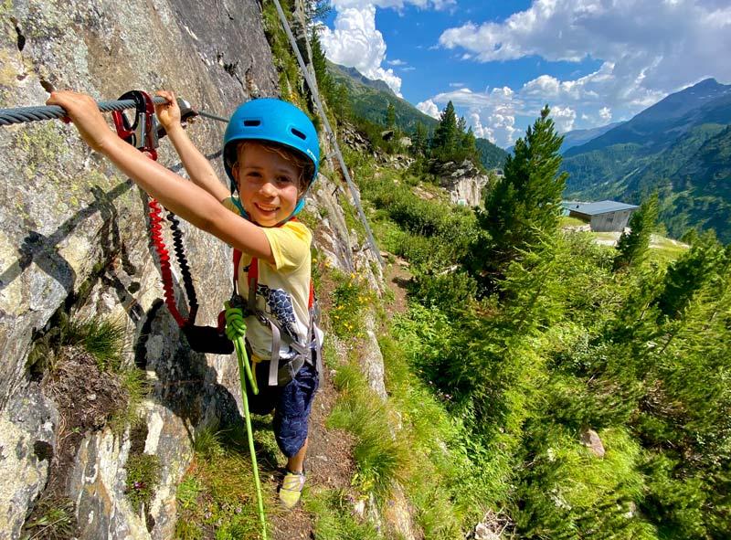 Das Bild zeigt eine Szene zum Thema Klettersteigsets Kinder. Ein Junge quert auf einem Klettersteig auf einem Grasband. Dabei wurd er zusätzlich mit einem Seil gesichert. Im Hintergrund grüne Wiese, Wald und ein türkis blauer Stausee.