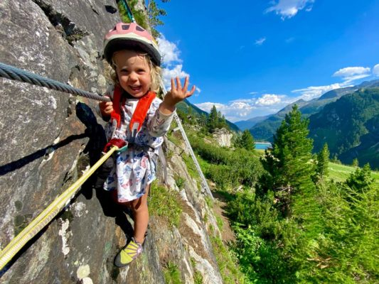 Das Bild zeigt ein dreijähriges Mädchen in einem Kleid auf einem Klettersteig. Es lacht in die Kamera und zeigt mit dem Finger nach oben. Im Hintergrund Wald, Wiese und ein Stausee sowie blauer Himmel.