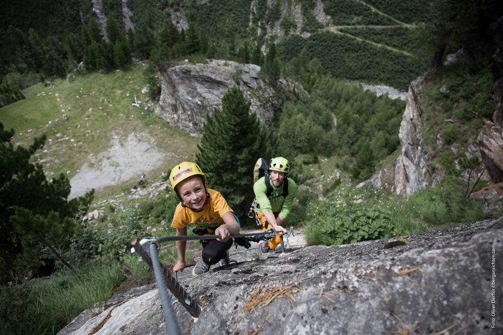Das bild zeigt den Einsatz eines Klettersteigsets Kinder auf einem Klettersteig. An einer grauen Wand klettert ein Junge mit gelbem Helm voraus. Dahinter der Vater. im Hintergrund eine grüne Wiese bzw. Wald.