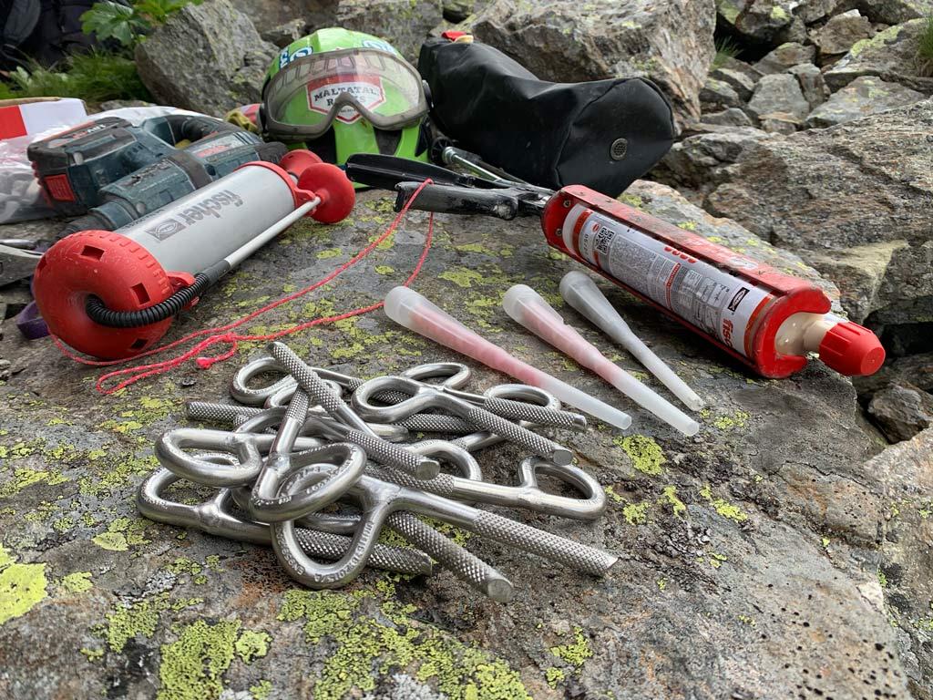 Das Bild zeigt Einbohrmaterial für einen Klettergarten. Im Vordergrund liegen einige Klebehaken, dahinter eine rote Auspresspistole mit Injektionsmörtel und ein Bohrloch Ausbläsrer.