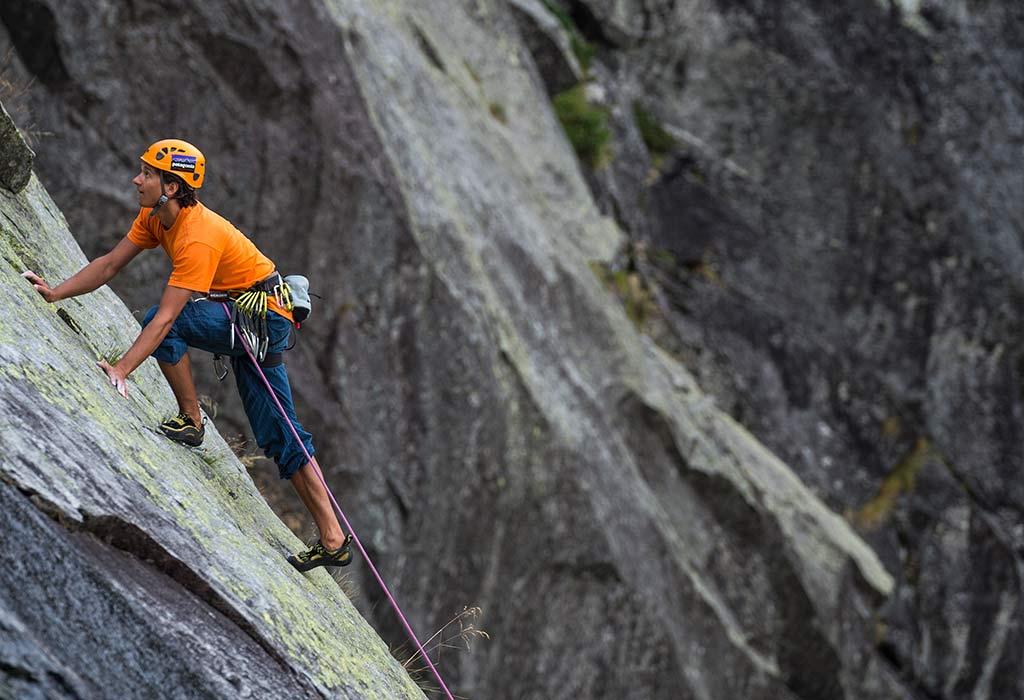 Das Bild zeigt ein Beispiel für perfekte Content Gestaltung. Ein Kletterer in auffälligem orangen Shirt klettert auf einer Felsplatte. Es soll zeigen, wie dynamisch junge Kletter Zielgruppen angesprochen werden sollen.