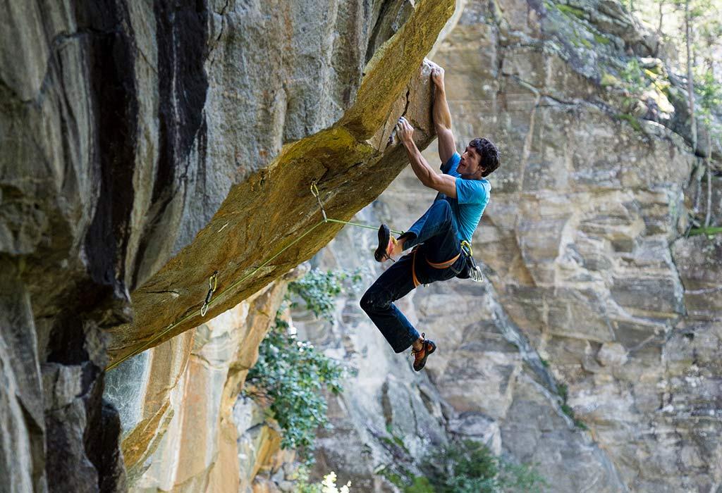 Das Bild zeigt einen Kletterer in blauer Bekleidung in einem Überhang. Es soll das Thema Kletter Infrastruktur widerspiegeln, indem man die Freude und aufmerksamkeit des Sportlers deutlich sehen kann.