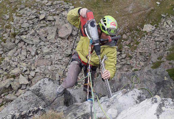 Das Bild zeigt einen arbeiter der als Beispiel für eine wichtige Kletter Infrastruktur einen Klettersteig errichtet. Er hängt im Seil und hält einen großen Bohrhammer mit einem Klettersteiganker an den Felsen.