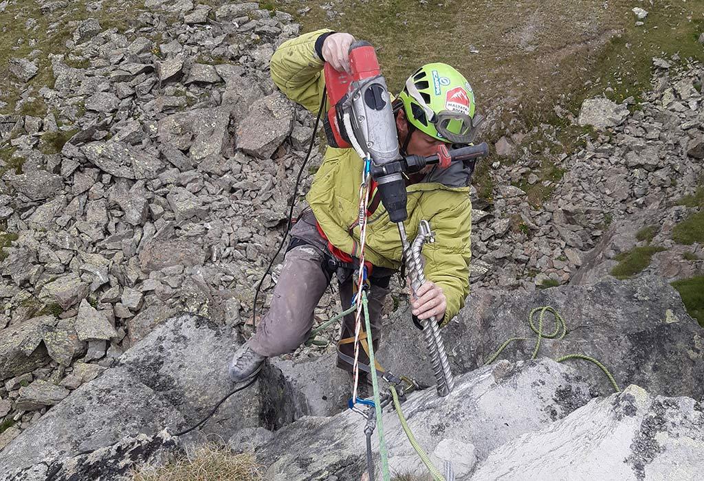 Das Bild zeigt einen Arbeiter beim Klettersteigbau. Er hängt im Seil und hält einen großen Bohrhammer mit einem Klettersteiganker an den Felsen um diese Kletter Infrastruktur zu errichten.