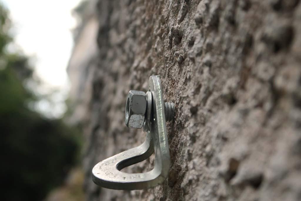 Das Bild zeigt einen Bohrhaken mit lockerer Laschein einer grauen Felswand. Das Bild soll die Problemlatik von lockeren Laschen in Klettergärten verdeutlichen.