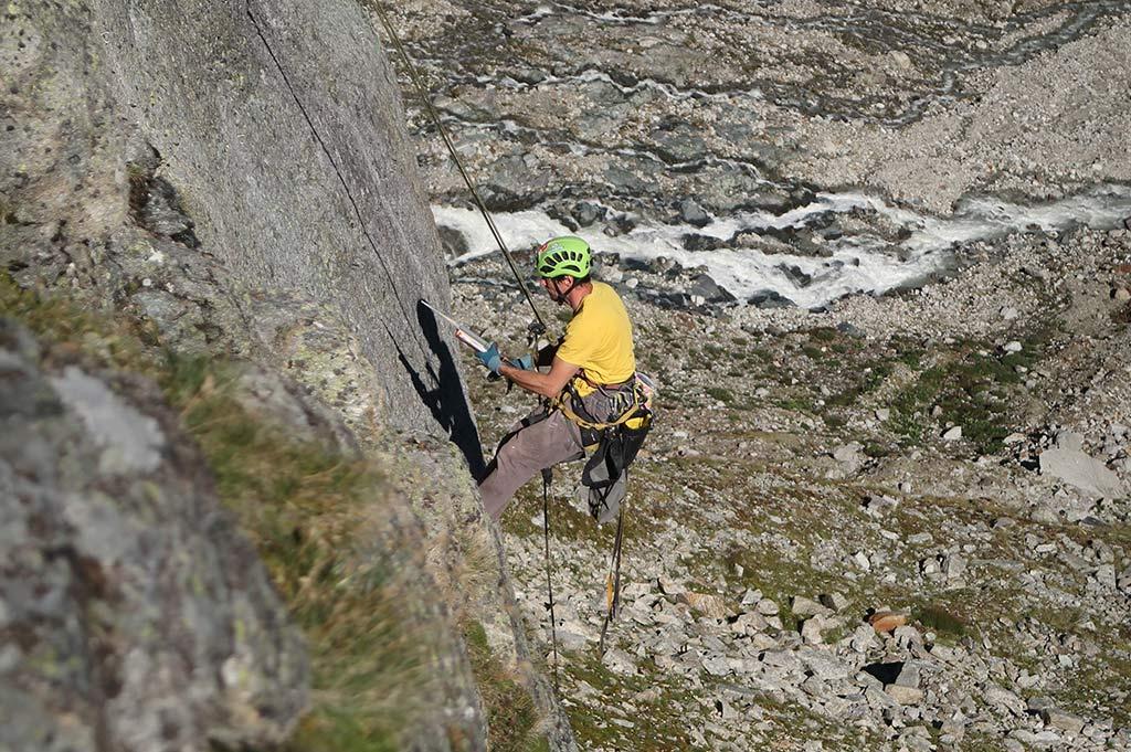 Das Bild zeigt einen Kletterer bei der Klettergarten Erschließung. Er hängt in einer grauen Felswand und klebt einen Klebehaken in die Wand. Im Hintergrund Felslandschaft und ein Gebirgsbach.