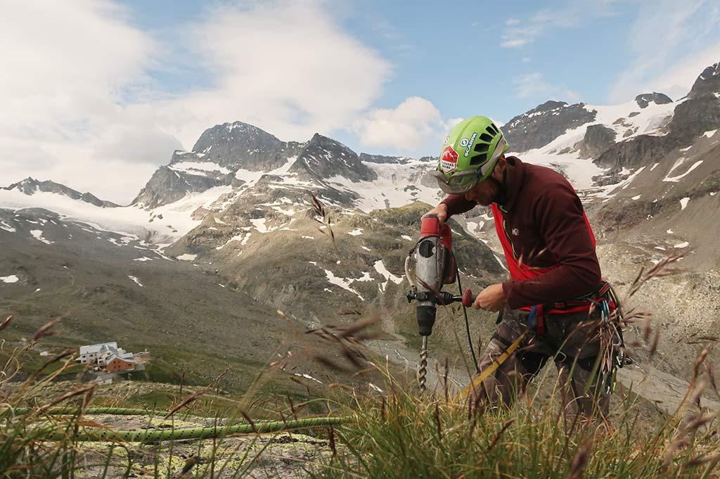Das Bild zeigt einen Arbeiter beim Klettersteigbau. Er steht auf einem Felsen und hält einen großen, roten Bohrhammer in den Händen. Im Hintergrund eine Hütte und eine imposante Gebirgslandschaft.