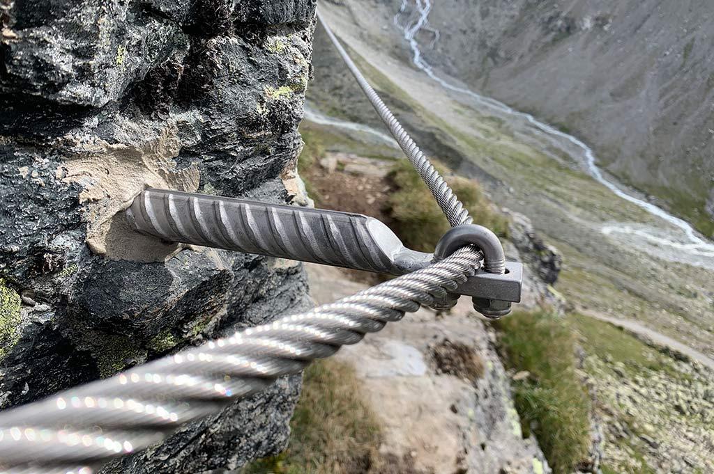 Das Bild zeigt den Einsatz von normgerechten Ankern bei der Klettersteig Errichtung. Man sieht einen Klemmanker an einer Felskante. Aus dem Vordergrund kommt ein Drahtseil und zieht über den Anker in Bildmitte in den Hintergrund.