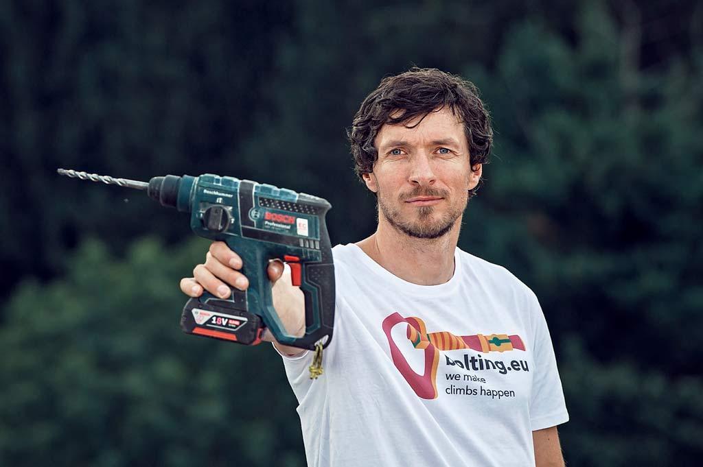 Das Bild zeigt den Betreiber des Einbohr Blog von bolting.eu und Geschäftsführer des Einbohrartikel Shops Gerhard Schaar. Er ist in einem weißem Shirt in Bildmitte zu sehen und hält eine Bohrmaschine in die Kamera.