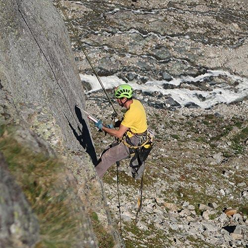 Das Bild zeigt einen Kletterer beim Einkleben eines Klebehakens in einer Kletterroute. In einer grauen Felswand hängt er am Seil und hantiert mit der Auspressppistole und dem Klebehaken. Er trägt ein gelbes T-Shirt. Im Hintergrund ein Gebirgsbach.