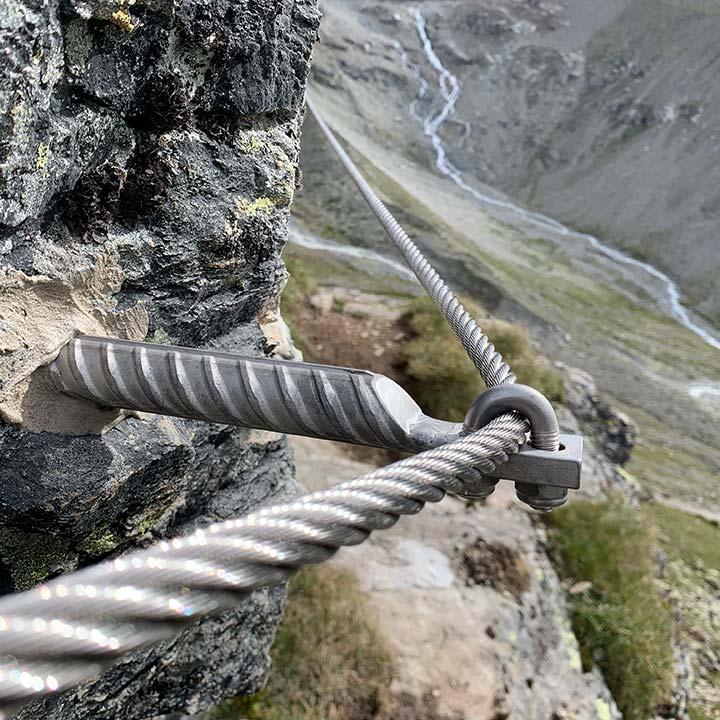 Das Bild zeigt ein Detail von einem Klettersteig. Ein Drahtseil läuft quer durch das Bild, es ist an einem Klemmanker befestigt. Im Hintergrund hochaline Landschaft.