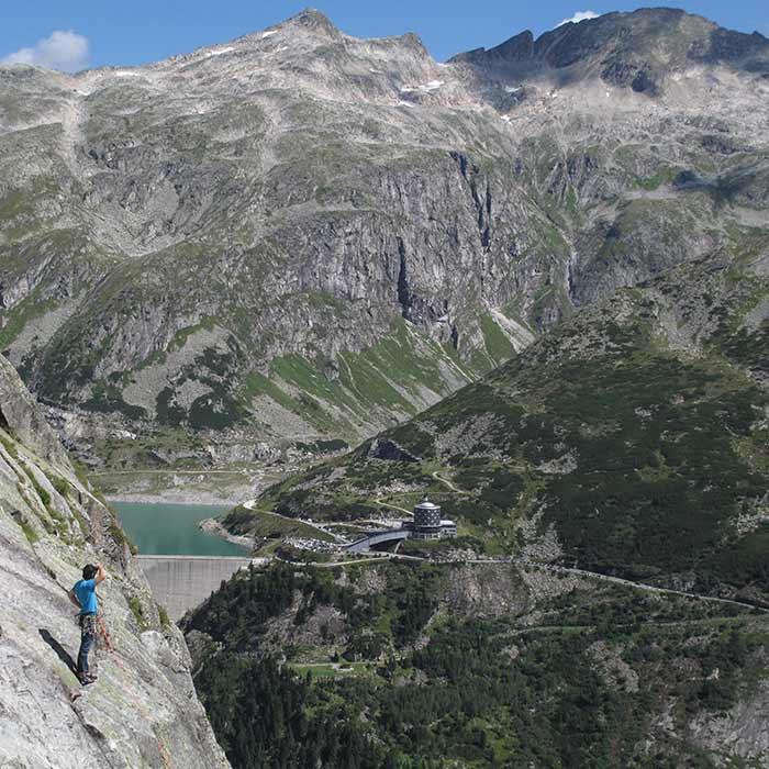 Das Bild zeigt ein Beispiel für eine klare Positionierung im Tourimus Marketing wenn es um Klettern geht. Ein Kletterer steht im GEbirge auf einem Felsband und blickt ins Tal. Dort steht eine Staumauer mit einem Hotel. Das Bild weckt Abenteuerlust und die Sehnsucht an diesem Ort zu klettern