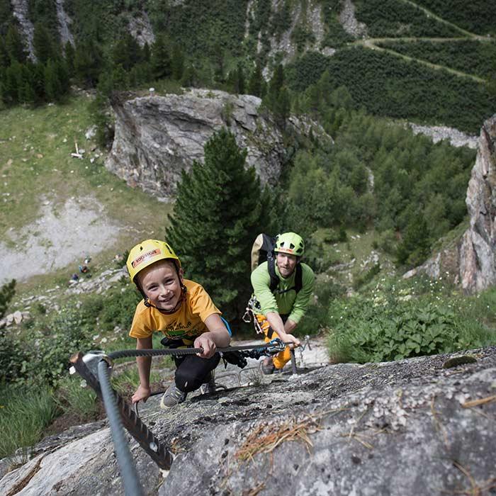 Das Bild zeigt einen Jungen der mit seinem VAter am Klettersteig unterwegs ist. Er lächelt in die Camera und hat sichtlich Spass am Sport. Im Hintergrund eine grüne Wiese, Felsen und Wald.