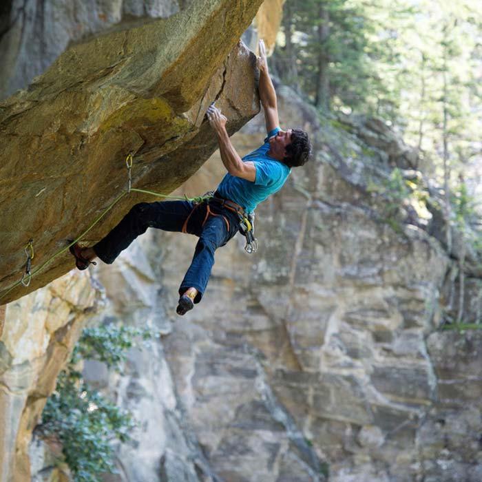Das Bild zeigt den Gründer von bolting.eu Tourismus Marketing Gerhard Schaar beim Klettern. Er hängt in einem überhängendem Felsen und springt zu einem Griff ober dem Körper.