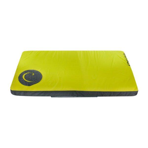 Das Bild zeigt die gelbe Edelrid Crux 3 Bouldermatte ausgelegt auf einem weißem Quadrat. Man erkennt die gelbe Oberseite, das Edelrid Logo sowie die schwarze Unterseite.