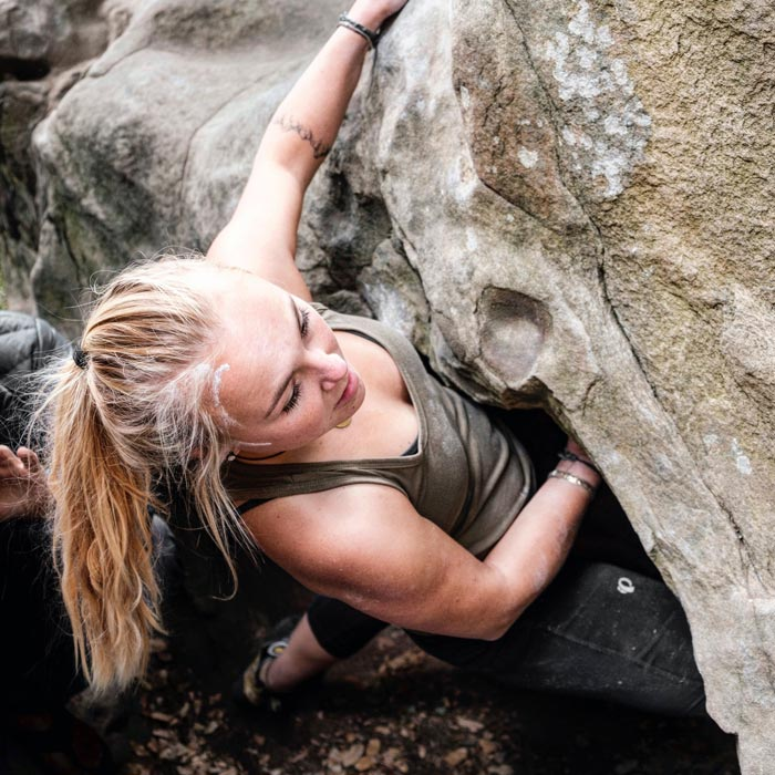 Das Bild zeigt bolting.eu Team Mitglied Laura Schröder. Sie bouldert im olivfarbenen -Shirt an einem braunen Sandsteinfels. Man erkennt ihren Oberkörper sowie ihre langen blonden Haare.