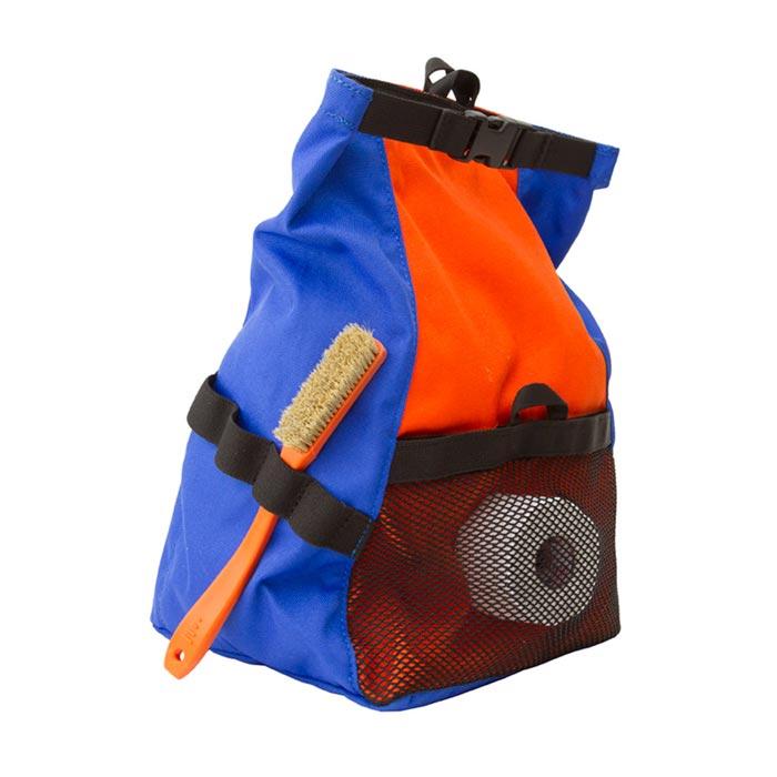 Das Bild zeigt das Metolius Chalk n´Roll Boulder Chalkbag in blau-orange. Man erkennt den Bag von der Seite, die Bürsten Halterungen mit einer orangen Bürste, den Top Verschluss sowie die Netztasche mit einem Tape.
