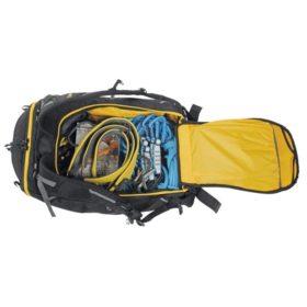 Das Bild zeigt einen geöffneten Climbing Pack mit allerlei Kletterausrüstung darin. Der Kletterrucksack liegt waagrecht im unteren Bildteil, mit dem geöffneten Deckel rechts.