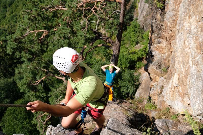 Das Bild zeigt ein gelungenes Beispiel für den Klettersteigbau für Anfänger. Ein Kletterer im Vordergrund zieht sich am Drahtseil hoch, im Hintergrund relaxed der andere an einen Baum lehnend.
