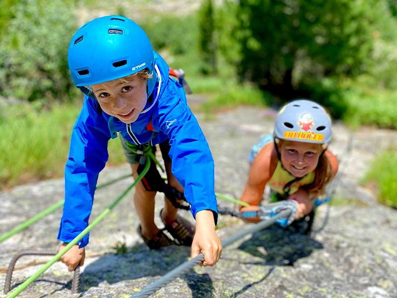 Das Bild zeigt ein Beispiel für die Klettersteig Errichtung für die Zielgruppe Kinder. Ein kleiner Junge und ein Mädchen lächeln in die Kamera und halten sich am Drahtseil fest.