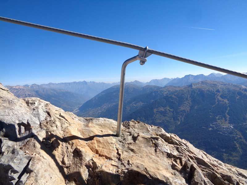 Das Bild zeigt den Klettersteigbau im hochalpinen Gelände anhand eines silbernen Klemmankers vor einer Bergkulisse und blauem Himmel.