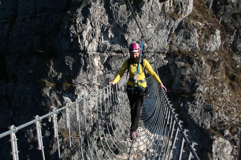 Das Bild zeigt eine Seilbrücke als Beispiel für modernen Klettersteigbau in den Dolomiten. Eine Frau balanciert über eine Drahtseilbrücke mit vielen silbernen Drahsteilen.