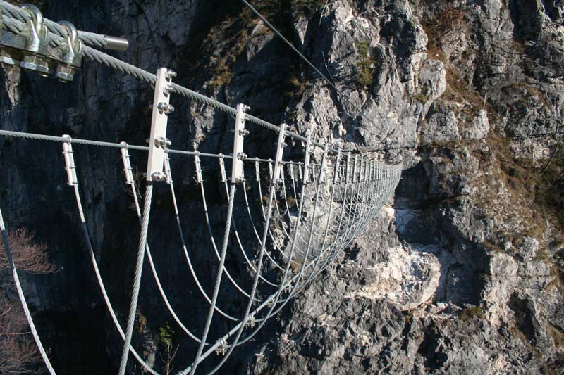 Das Bild zeigt eine Tibetan Bridge als Beispiel für modernen Klettersteigbau. Man sieht eine Drahtseilbrücke aus silbernen Seilstücken über eine Schlucht.