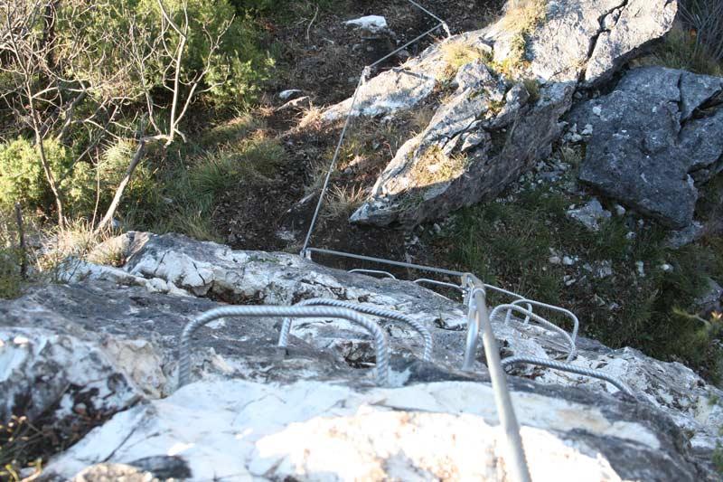 Das Bild zeigt die Klettersteig Errichtung mit massivem Einsatz von Trittbügeln und Griffbügeln an einer grauen Felswand.