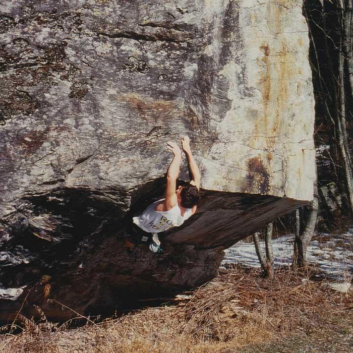 Das Bild zeigt einen Boulderer beim Klettern auf einen Granitblock im Jahre 1995 mit einem selbtsgemachten Boulder Chalkbag um die Hüfte.