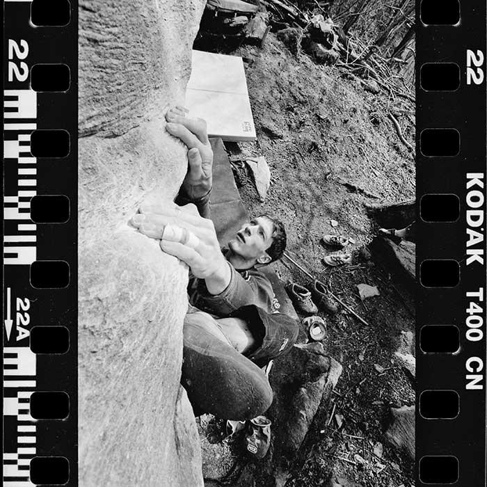 Das Bild zeigt einen gescannten Schwarz-Weiss Film mit einem Boulderer darauf. Im Hintergrund liegen ein paar Bouldermatten am Boden.