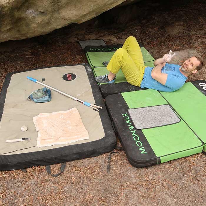 Das Bild zeigt einen lächelnden Boulderer auf einer MAtte mit Boulder Zubehör bei seinen Beinen.