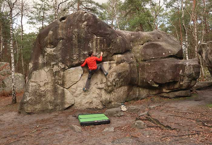 Das Bild zeigt den VErwendungszweck einer Bouldermatte. Ein Kletterer steigt auf einen Felsblock und hat unterhalb am Boden die Matte als Schutz hingelegt.