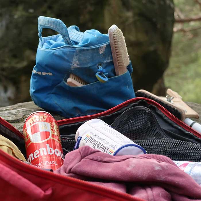 Zu sehen ist ein Bild zum Thema Chalkbag Bouldern. Im Vordergrund sieht man einen geöffneten Kletterrucksack mit einer Dose Bier und einem Theraband, im Hindergrund ein Boulder Chalkbag.