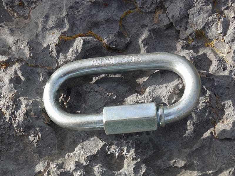 Das Bild zeigt ein Schraubglied - Rapidglied ohne Norm mit einer Bruchlast von nur 200kg auf einem grauem Fels.