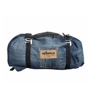 Das Bild zeigt den Jeans Seilsack Mantle in dunkler Farbe. Man sieht ihn von der Seite und erkennt das Logo, die Kompressionsriemen und die Alu Schnallen.