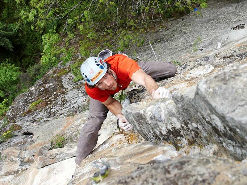 Das Bild zeigt einen Kletterer mit rotem T-Shirt und hellblauen Kletterhelm in einer Mehrseillängenroute.