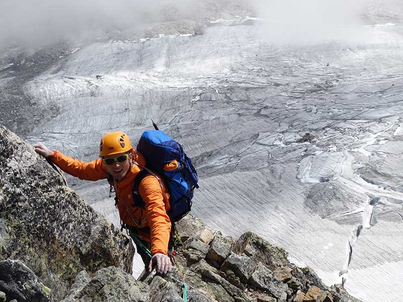 Das Bild zeigt einen Kletterer auf einem Granitgrat über einem Gletscher. Er trägt einen orangen Kletterhelm und Jacke.