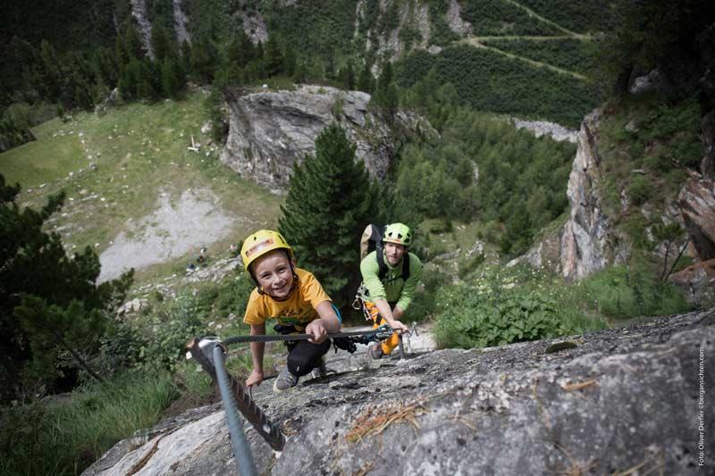 Das Bild zeigt einen kleinen Jungen mit seinem Vater am Klettersteig. Sie tragen beide vorbildlich Kletterhelme als Schutz für den Kopf.