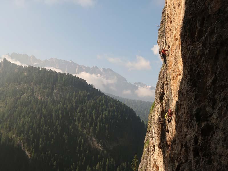 Das Bild zeigt eine Seilschaft an einer Felswand in den Dolomiten. Im Hintergrund ragen Felsspitzen in den wolkigen Himmel.
