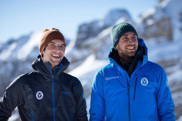 Das Bild zeigt die beiden Bergführer der Alpinschule Animont, Oliver Rohrmoser und Armin Fuchs in blauen Jacken vor einer winterlichen Bergkulisse.