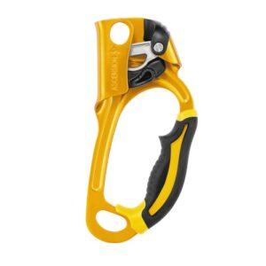 Das Bild zeigt die gelbe Petzl Ascension Handsteigklemme. MAn sieht die gesamte Innenseite mit Griff, Klemmnocken, Fixierhebel und Karabinerösen.